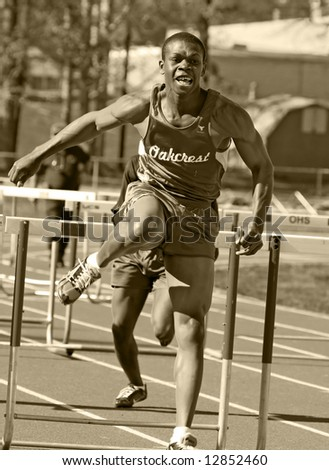 male runner competing during hurdles - stock photo