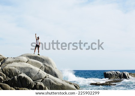 Male runner exploded to the top hill resting after run, successful winner standing on big hill enjoying the sun and life freedom, win over self, male runner exploded to the top hill, runner resting - stock photo