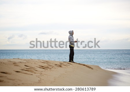 Male runner having rest after run while holding smart phone with headphones and enjoying beautiful sea landscape view outdoors,sporty young man standing on the beach while taking break during workout - stock photo