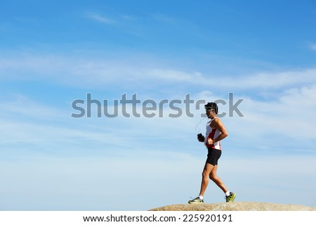 Male runner in sportswear running down over the rocks on sky background, healthy lifestyle and sport concept - stock photo
