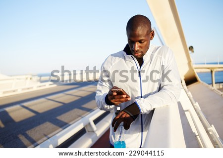 Male runner in white windbreaker typing something on his mobile smart phone standing at sunset on beautiful road, black man holding smart phone resting typing something, fit man with mobile smartphone - stock photo