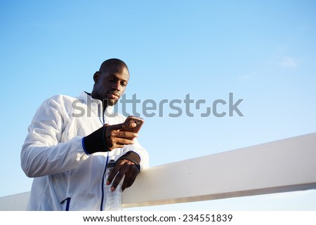 Male runner in white windbreaker typing something on his mobile smart phone standing at sunset on beautiful road, black man holding smart phone resting typing something,fit man with mobile smart phone - stock photo