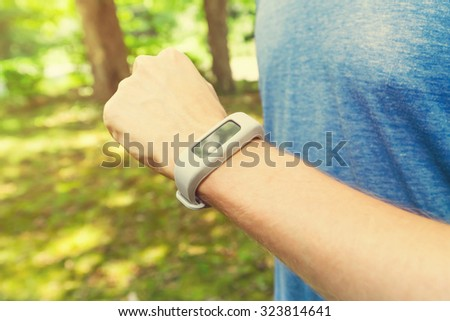 Male runner jogging outside looking at his wearable fitness tracker at sunset