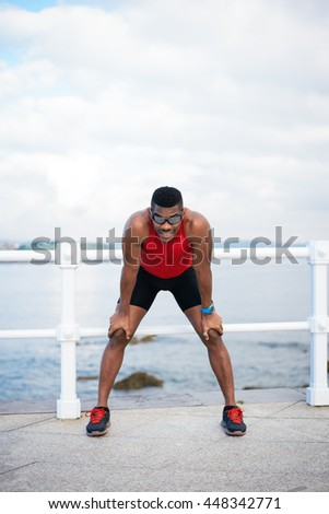 Male runner resting. Black man taking a running workout break for breathing. Sport motivation concept.