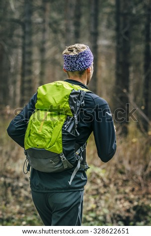 male runner running in autumn forest, behind him a large backpack. view from back