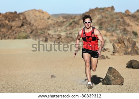 Male runner running / sprinting fast during adventure marathon run in beautiful desert landscape. Strong fit muscular fitness sport man model. - stock photo