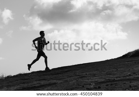 Male runner sprinting up a hill.