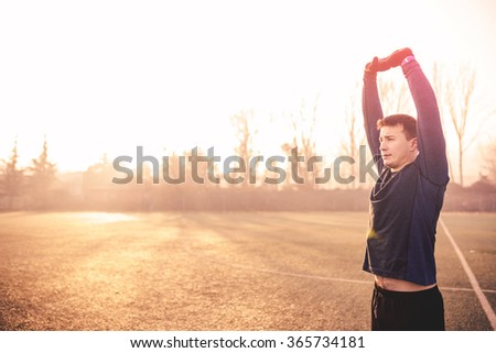 Male runner stretching after running in cold weather wearing running clothing. Depth of field, focus only on man. - stock photo