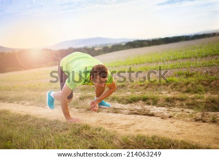 Male runner tripping over and falling down on the cross country trail - stock photo