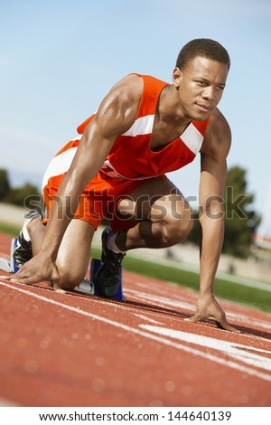 Male runner waiting at the starting block on race track