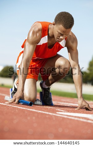 Male runner waiting at the starting block with a baton on racing track - stock photo