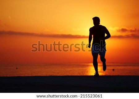 Male runner with muscular body running alone at orange sunrise on the beach, fitness training on the beach, beautiful runner silhouette in action, fitness and healthy lifestyle