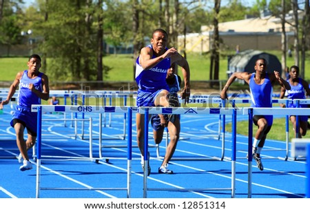 male runners competing during hurdles - stock photo