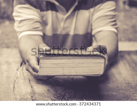 male's hands holding the old book on old wooden table - stock photo