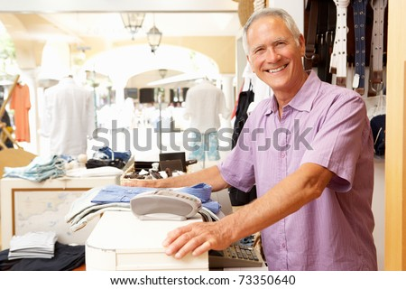 Male Sales Assistant At Checkout Of Clothing Store - stock photo