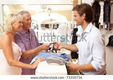 Male Sales Assistant At Checkout Of Clothing Store With Customers - stock photo
