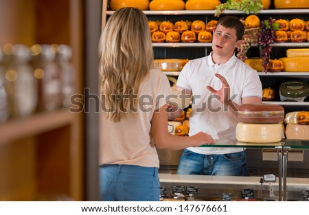 Male salesman in cheese store with a female customer talking about his products and helping to choose delicious cheese - stock photo
