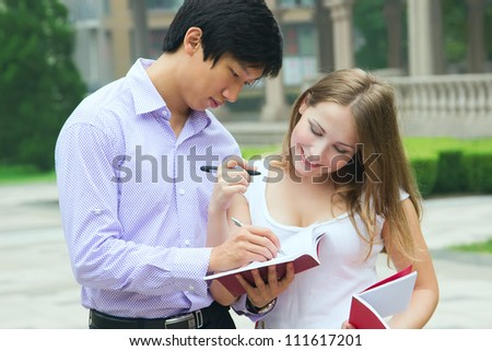 Male school teacher explain something to female student. People look at book and study together - stock photo