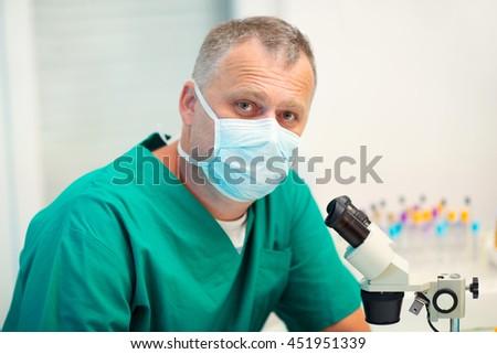Male scientific researcher using microscope in the laboratory, selective focus - stock photo