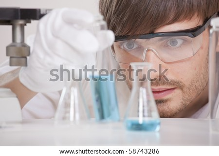 male scientist in research lab holding glass flask with blue fluid - stock photo