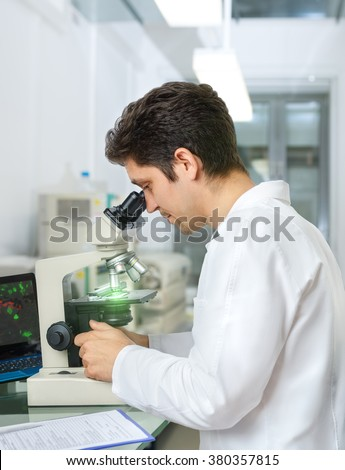 Male scientist or tech with dark hair and brown eyes works with microscope samples in research facility - stock photo