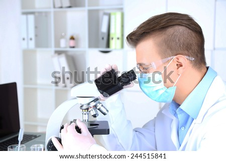 Male scientist using microscope in laboratory