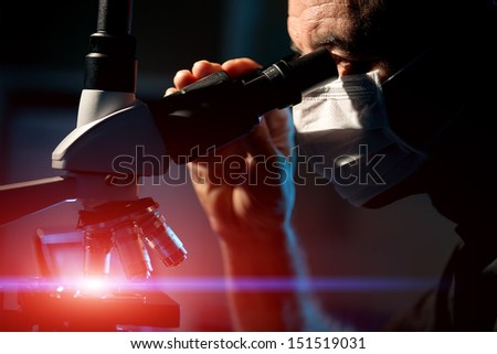 Male scientist watch  in  microscope for  microbiological structures - stock photo
