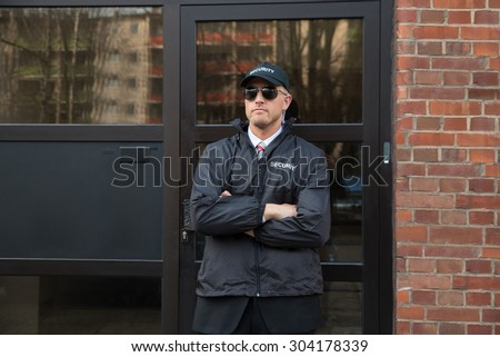 Male Security Guard Standing In Uniform With Armcrossed In Front Of The Entrance - stock photo