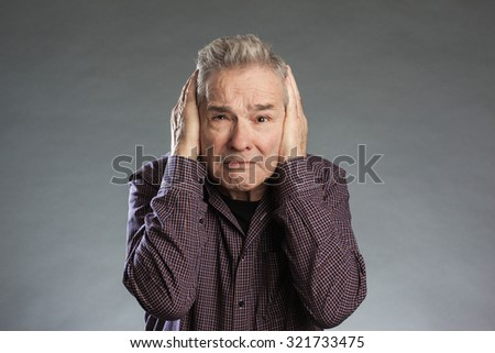 Male senior holding hands over ears. Horizontal portrait on gray background with copy space - stock photo
