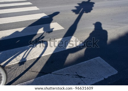 Male senior pedestrian waiting for green light by an urban zebra crossing while a cyclist hurry by. - stock photo