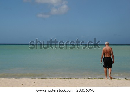 Male senior walks from a deserted beach into the sea - stock photo