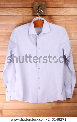 Male shirt on hanger on wooden wall background