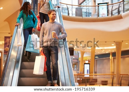 Male Shopper On Escalator In Shopping Mall - stock photo