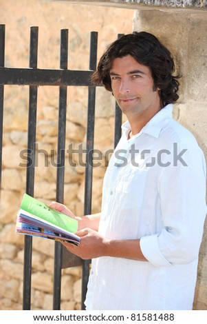 Male sightseer consulting a brochure - stock photo
