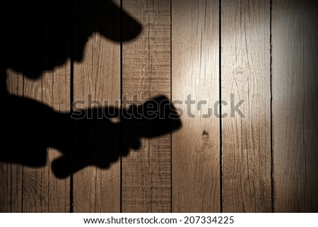 Male silhouette with searchlight on wooden wall. You can see more crime scene in my set - stock photo