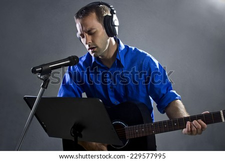 male singer holding a guitar and wearing headphones on concrete background - stock photo
