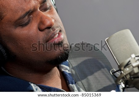 Male singer wearing headphones and singing into a studio condenser microphone equipped with a pop filter - stock photo