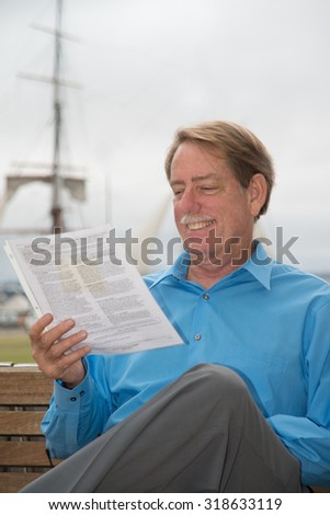 Male sitting on a bench, reading court papers and smiling.