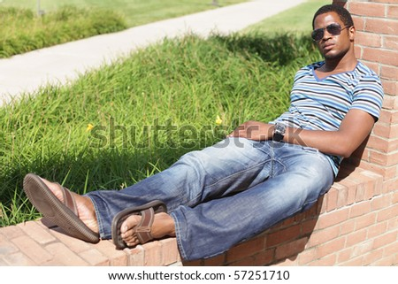 Male sitting on brick - stock photo