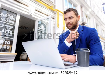 male sitting outside of a cafe with computer