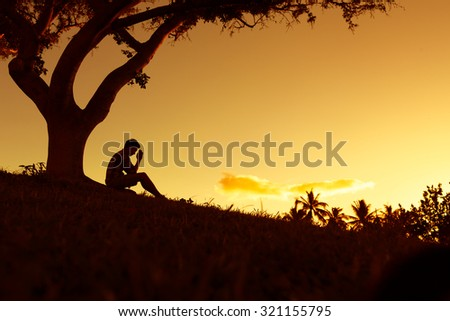 Male sitting under a tree clasping his hands together.  (Praying and feeling desperate concept) - stock photo