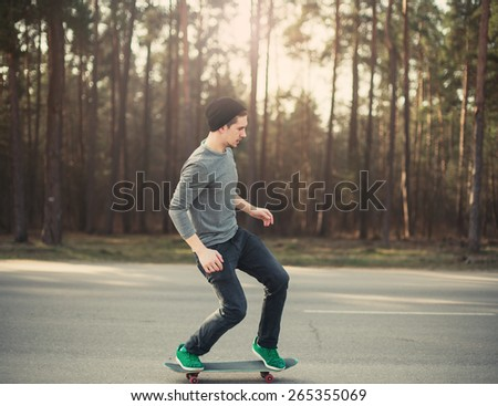 male skateboarder skating in the park at sunset - stock photo