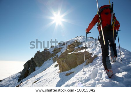 Male ski-climber climbing a snowy ridge; horizontal frame. Italian alps. - stock photo