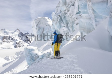 Male ski-climber standing in front of the highest peaks of Monte Rosa (4664 mt) during an high altitude hiking in the Schwartztor Glacier. Zermatt, Switzerland. Exploring and adventure concept. - stock photo