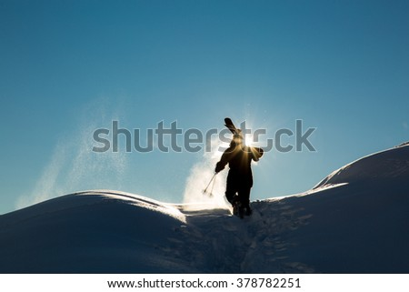 male skier carries skis in the snow on winter day at the ski resort in Georgia - stock photo