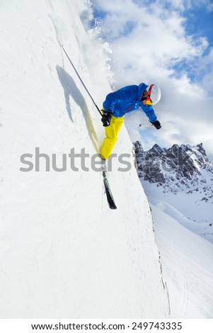 Male skier on downhill free-ride with sun and mountain view - stock photo