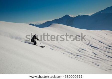 Male skier skiing in fresh snow on ski slope on a sunny winter day at the ski resort in Georgia - stock photo