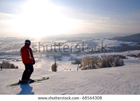 Male skier standing on slope. Winter mountain landscape. Bright sunlight. - stock photo