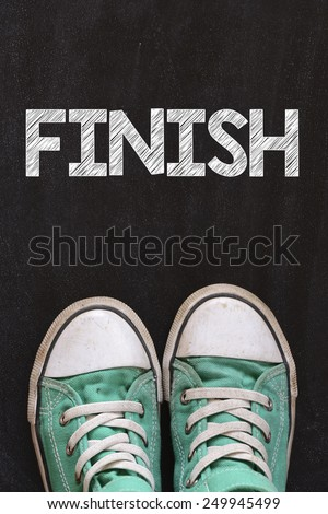 Male sneakers and word finish. Male sneakers on the asphalt road with drawn word finish - stock photo