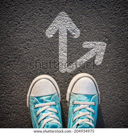Male sneakers on the asphalt road with drawn direction arrow - stock photo